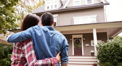 Couple standing in front of New house